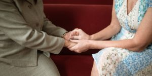Forgiveness / Holding hands in church pew.